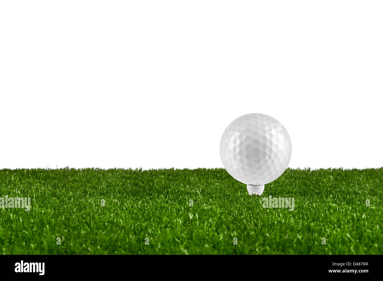 golf ball on tee on grass - Stock Image