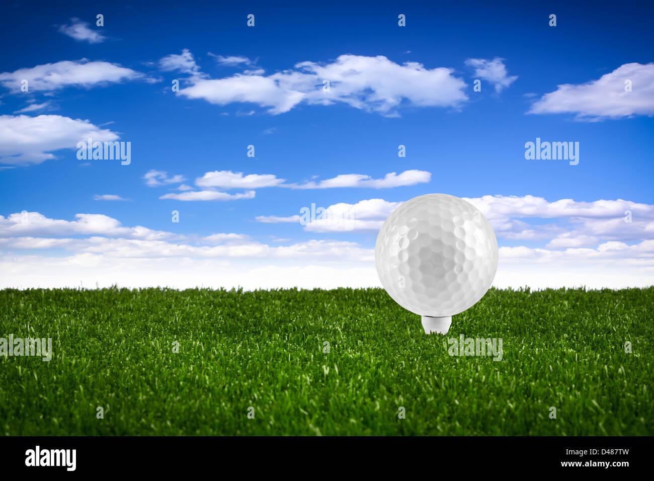 golf ball on tee on gras - Stock Image