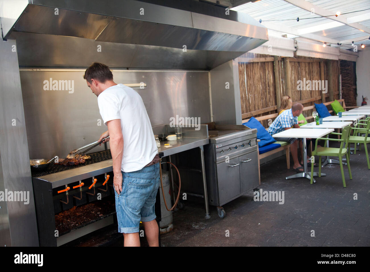 The Backyard Cape Town grilling meat at backyard restaurant in sea point - cape town stock