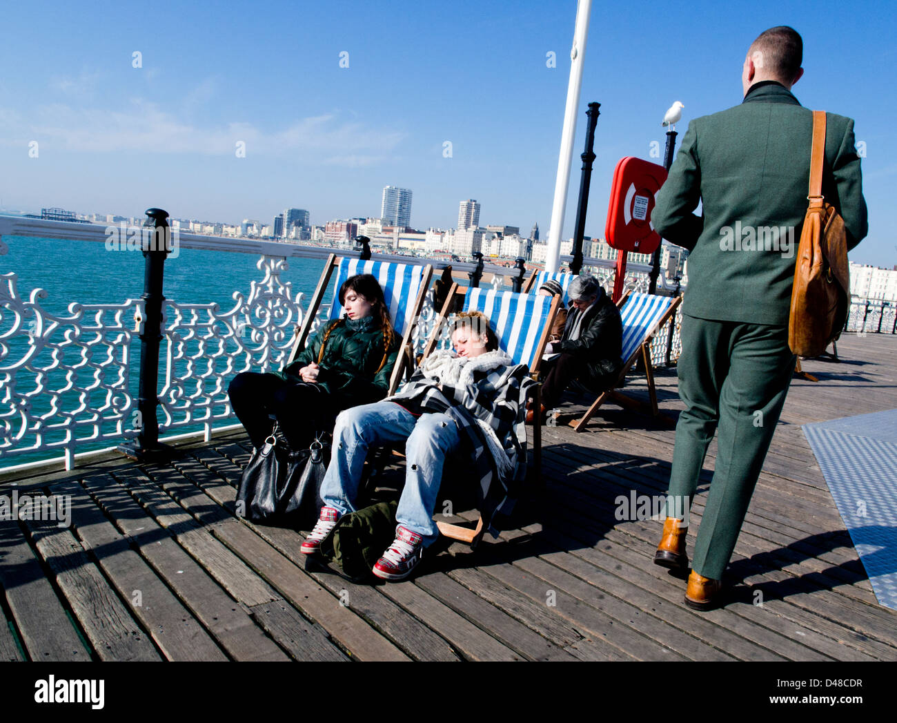 Two student girls snoozing on deckchairs in the spring sunshine on Brighton Pier - Stock Image