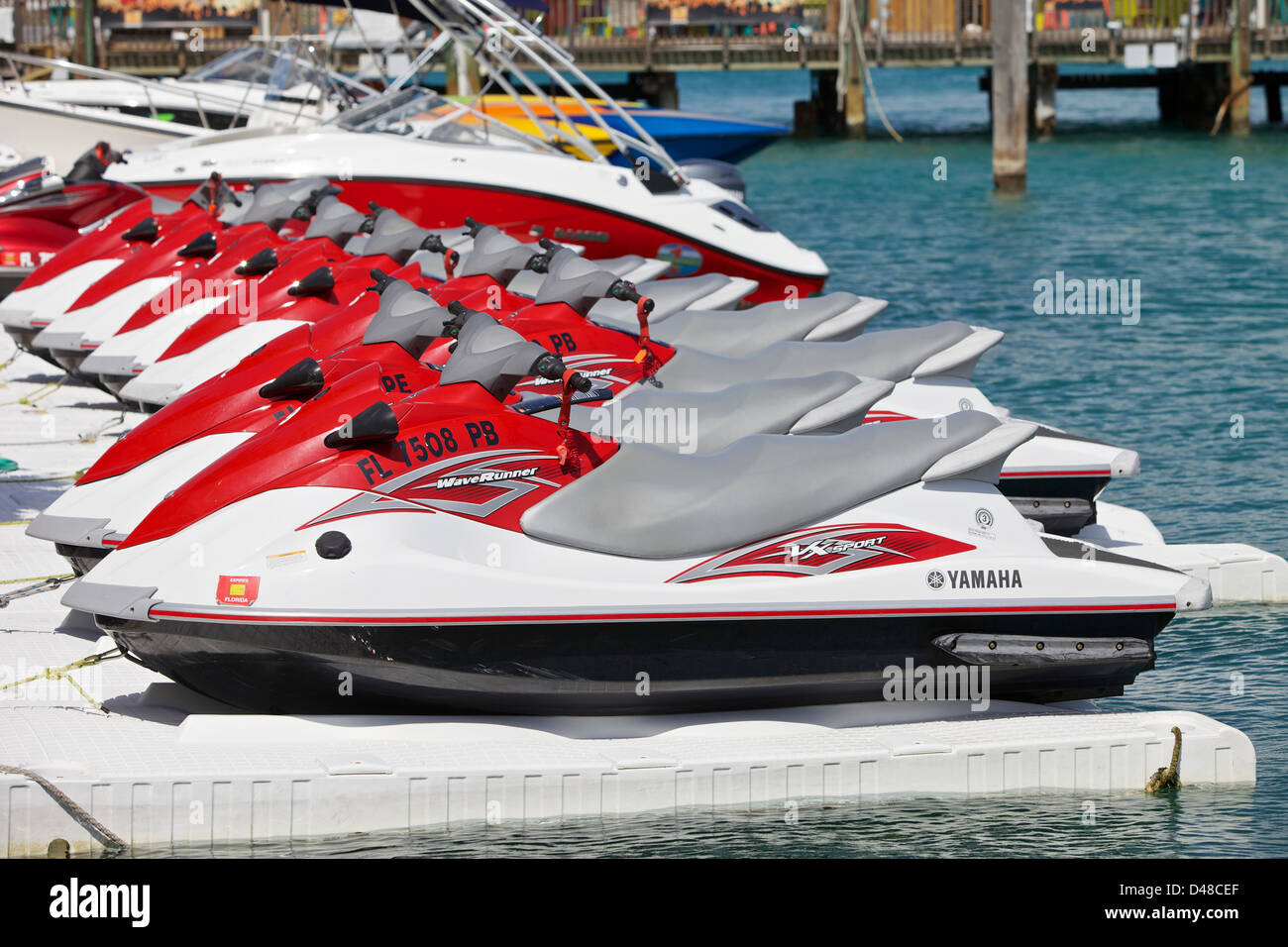 Personal watercraft lined up in a harbor - Stock Image
