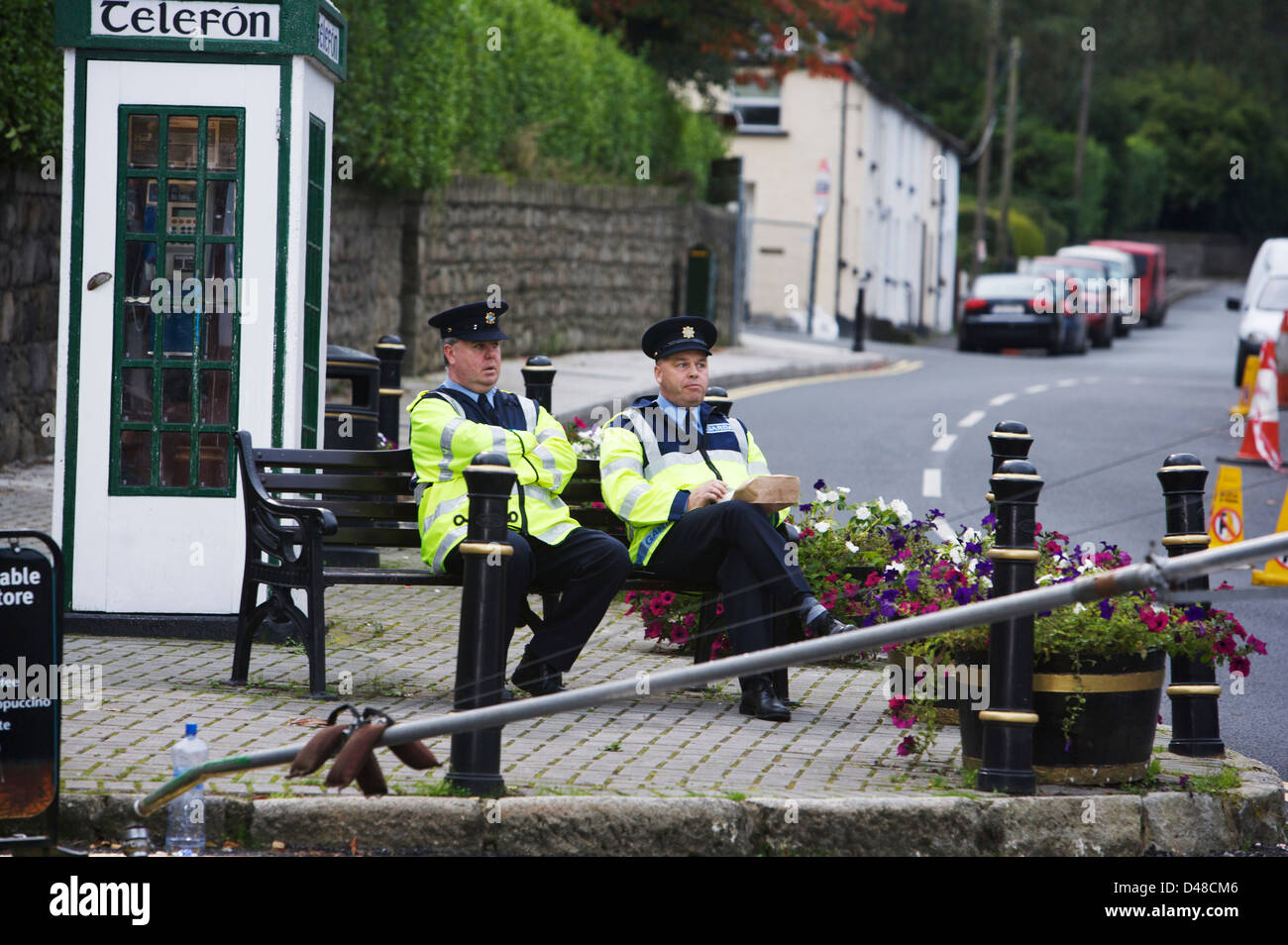 Two Irish Gardai sitting on a park bench in the picturesque village of Enniskerry in Wicklow Ireland Stock Photo