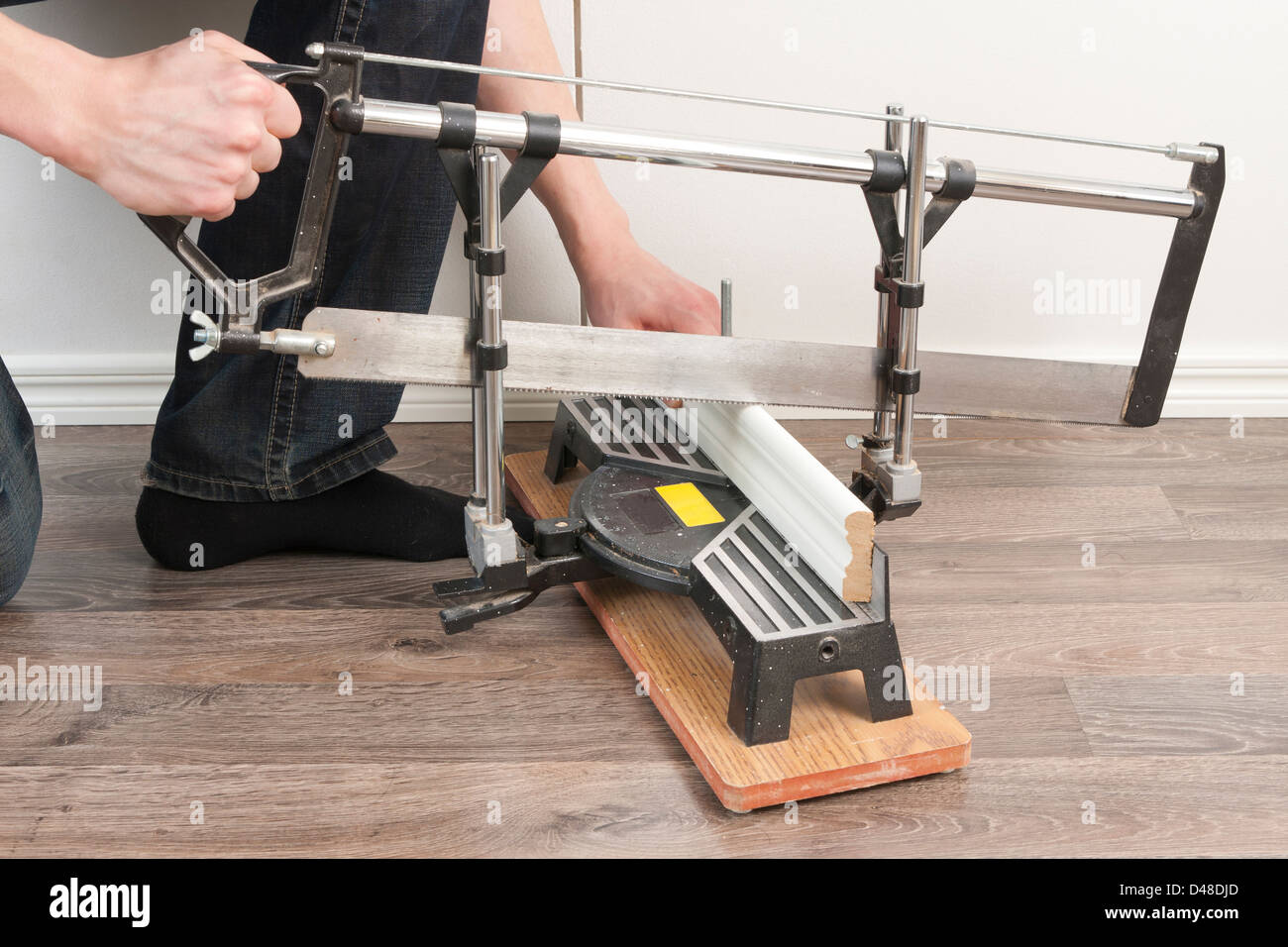 Worker Sawing Mopboard - Stock Image