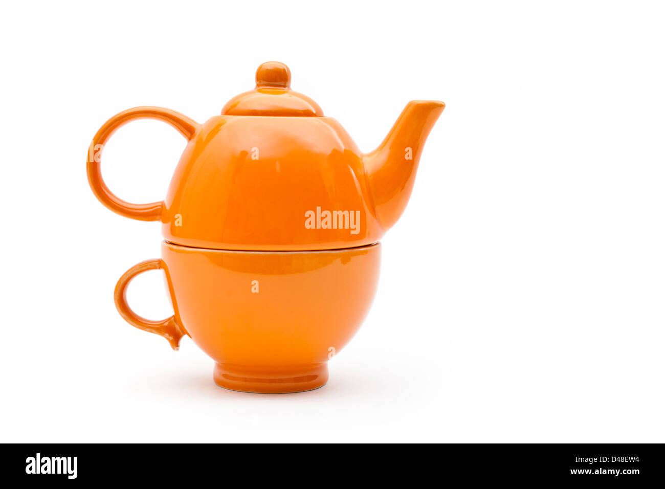 Orange teapot and teacup set isolated on a white background. Tea pot designed to sit on top of the cup. - Stock Image