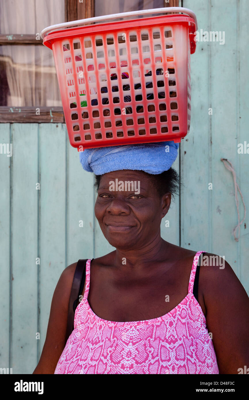 Woman from Vieux Fort village, St Lucia carrying her messages in a red plastic box and on her head - Stock Image