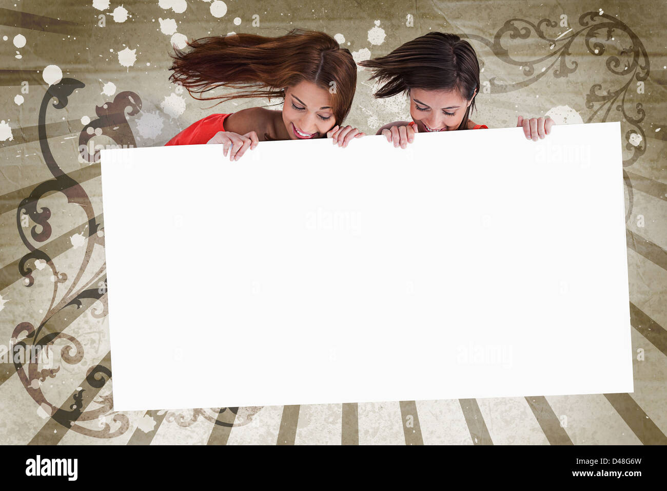 Young girls looking down at white copy space screen Stock Photo