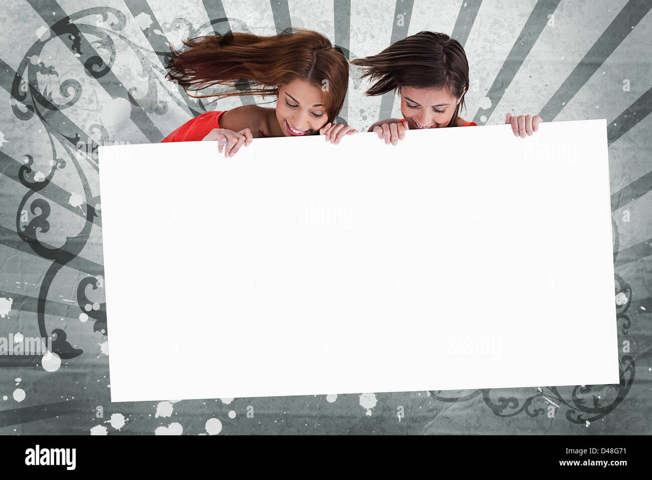 Pretty girls looking down at white copy space screen Stock Photo