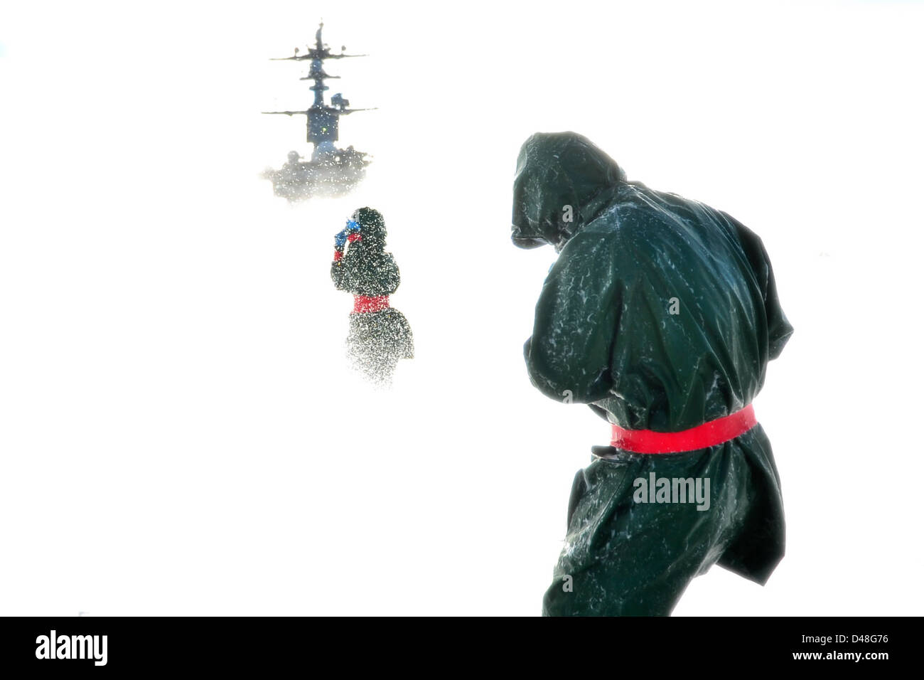 Sailors participate in a flight deck washdown at sea. - Stock Image