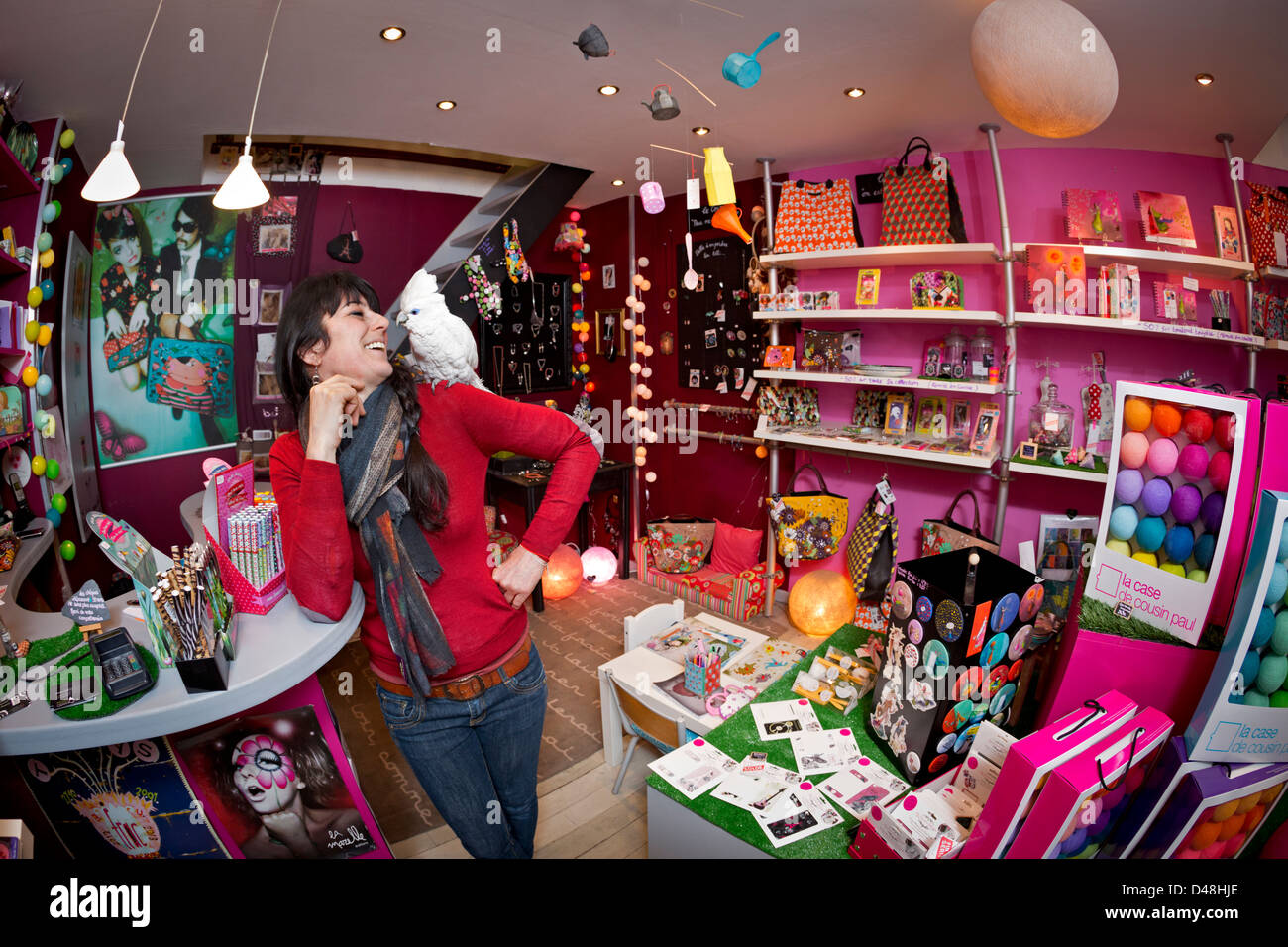 At Vichy, a young woman with her bare-eyed cockatoo (Cacatua sanguinea) in a shop of decoration and fashion accessories - Stock Image