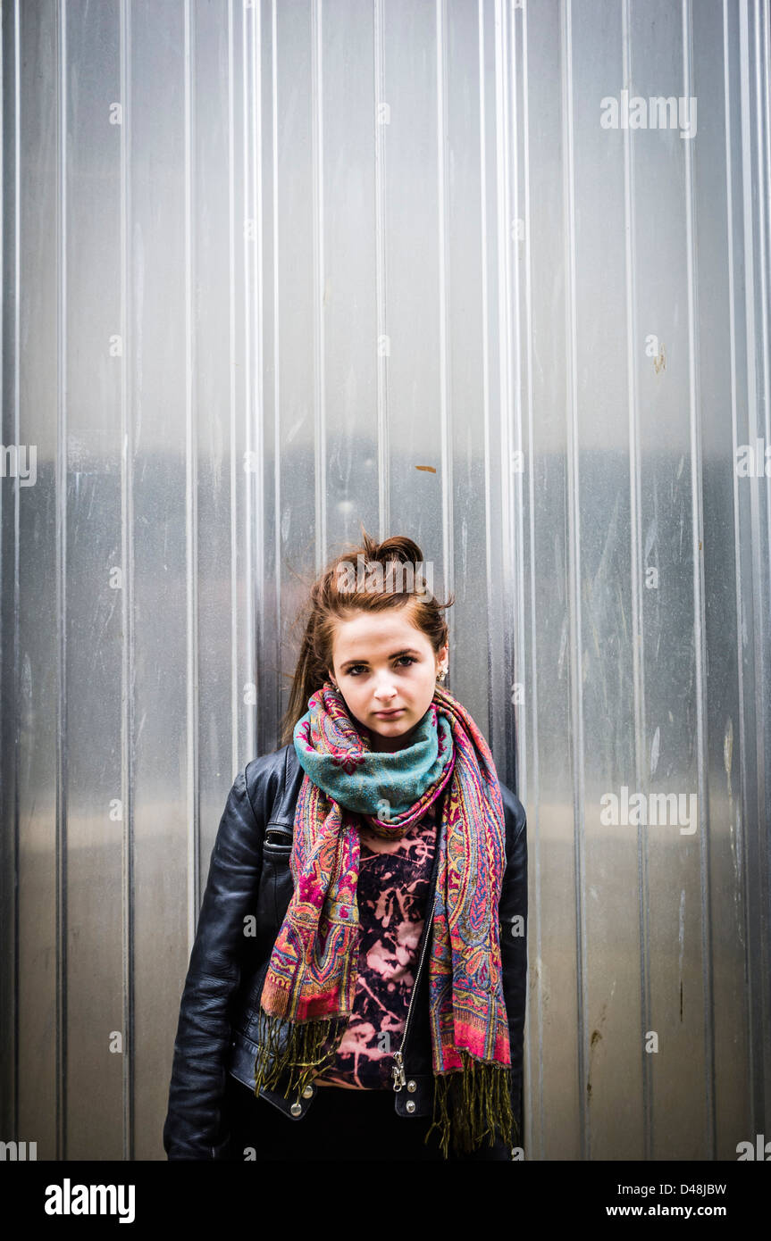 a 14 15 year old teenage girl wearing a leather jacket standing in front of metal clad wall, UK - Stock Image