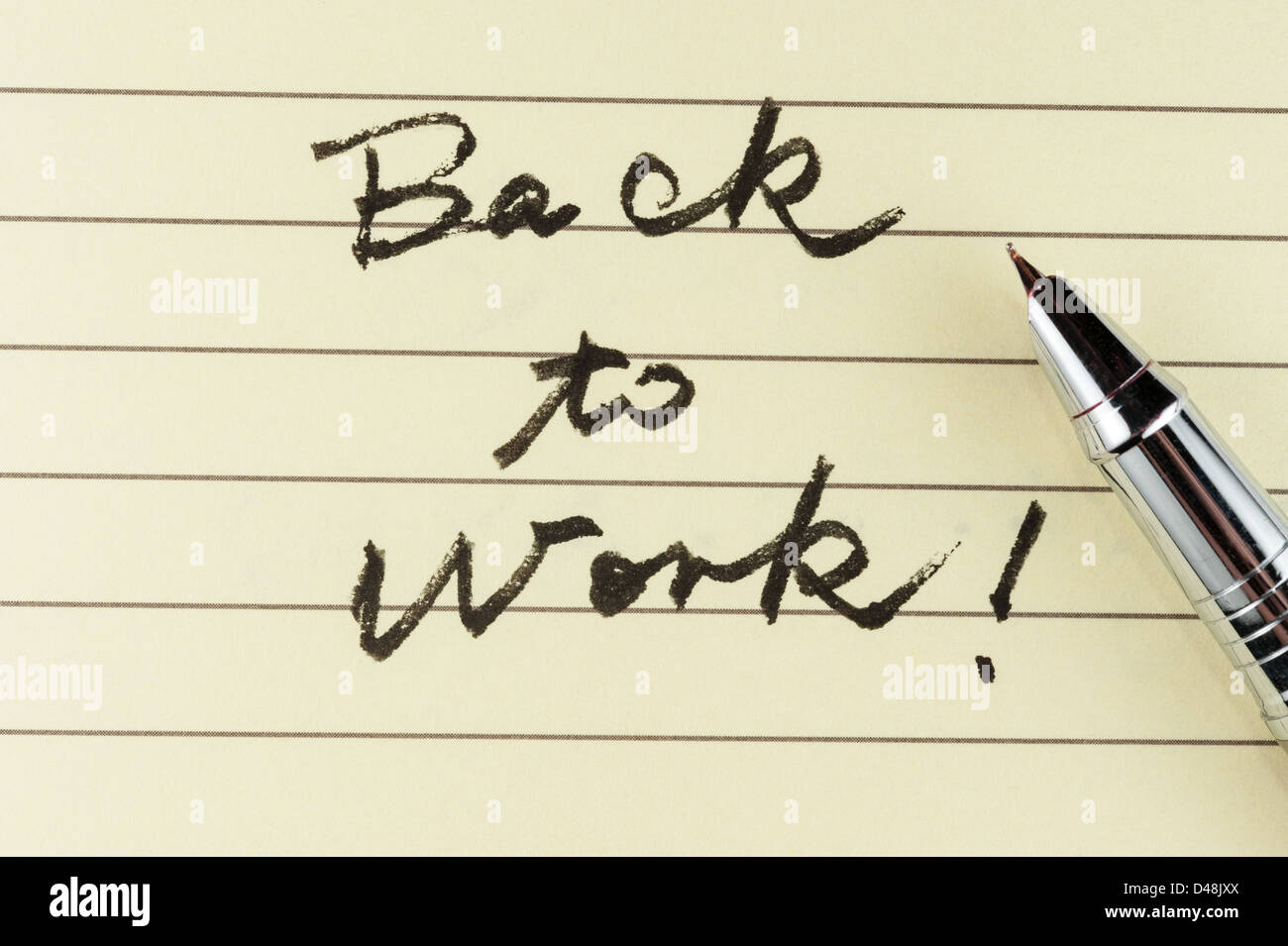 back to work words written on lined paper with a pen on it stock
