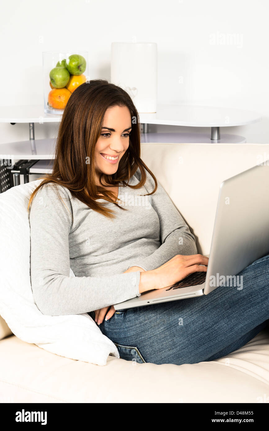 attractive relaxed woman is working at home on a sofa - Stock Image