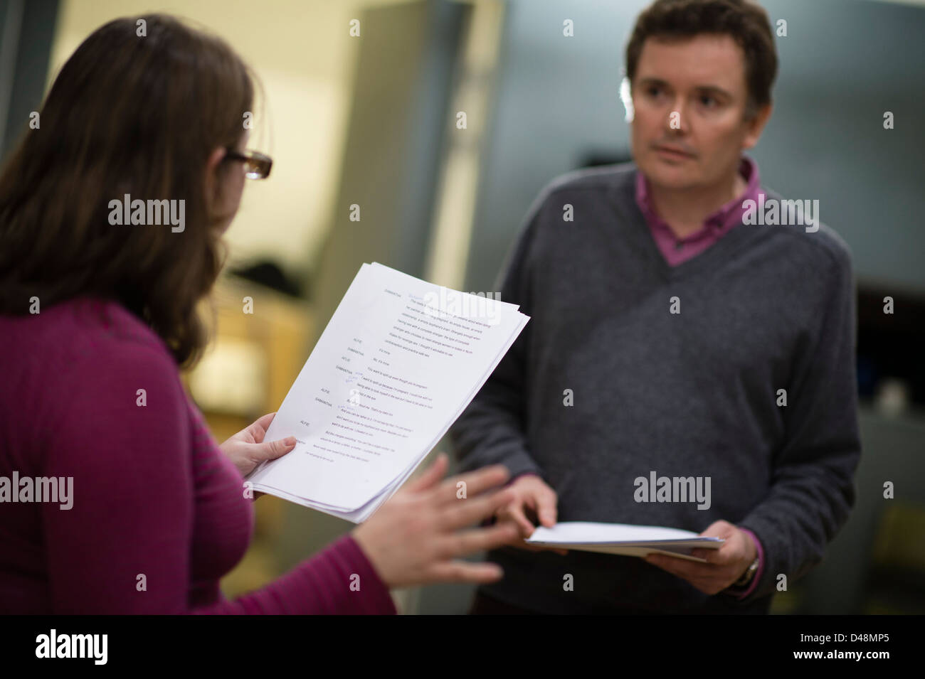 two Actors in rehearsal, holding their scripts, reading lines of dialogue from a new play, UK - Stock Image
