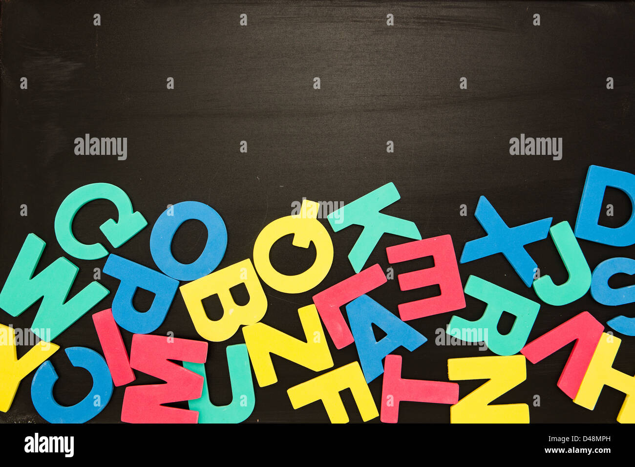 Alphabet magnets in a jumble on blackboard - Stock Image