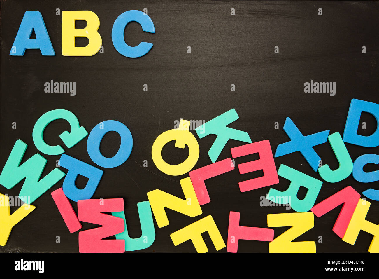 Alphabet magnets in a jumble on blackboard with Abc in order - Stock Image