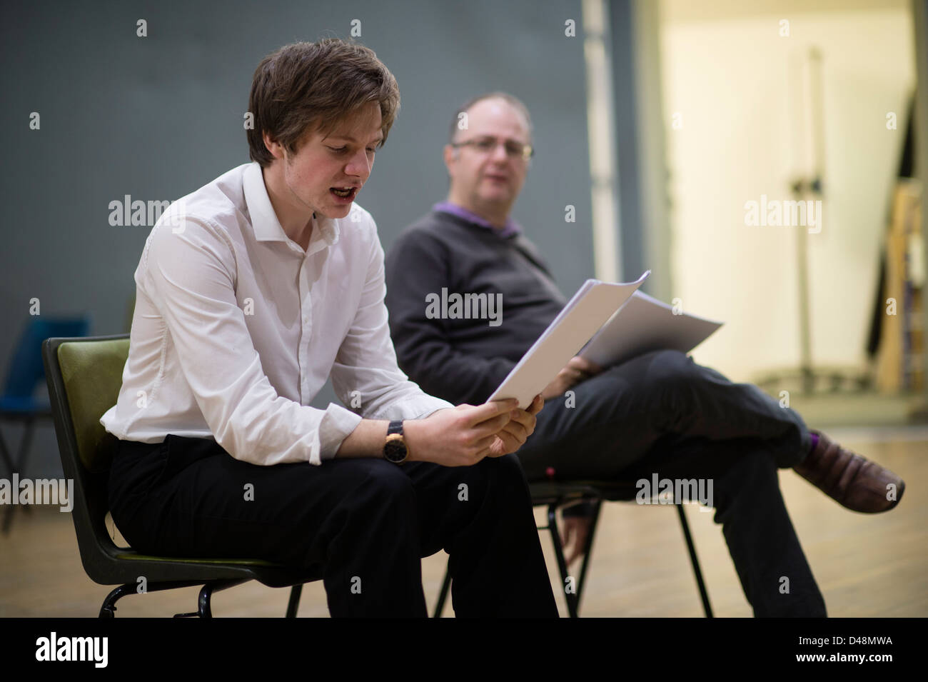 Actors in rehearsal, holding their scripts, reading lines of dialogue from a new play, UK - Stock Image