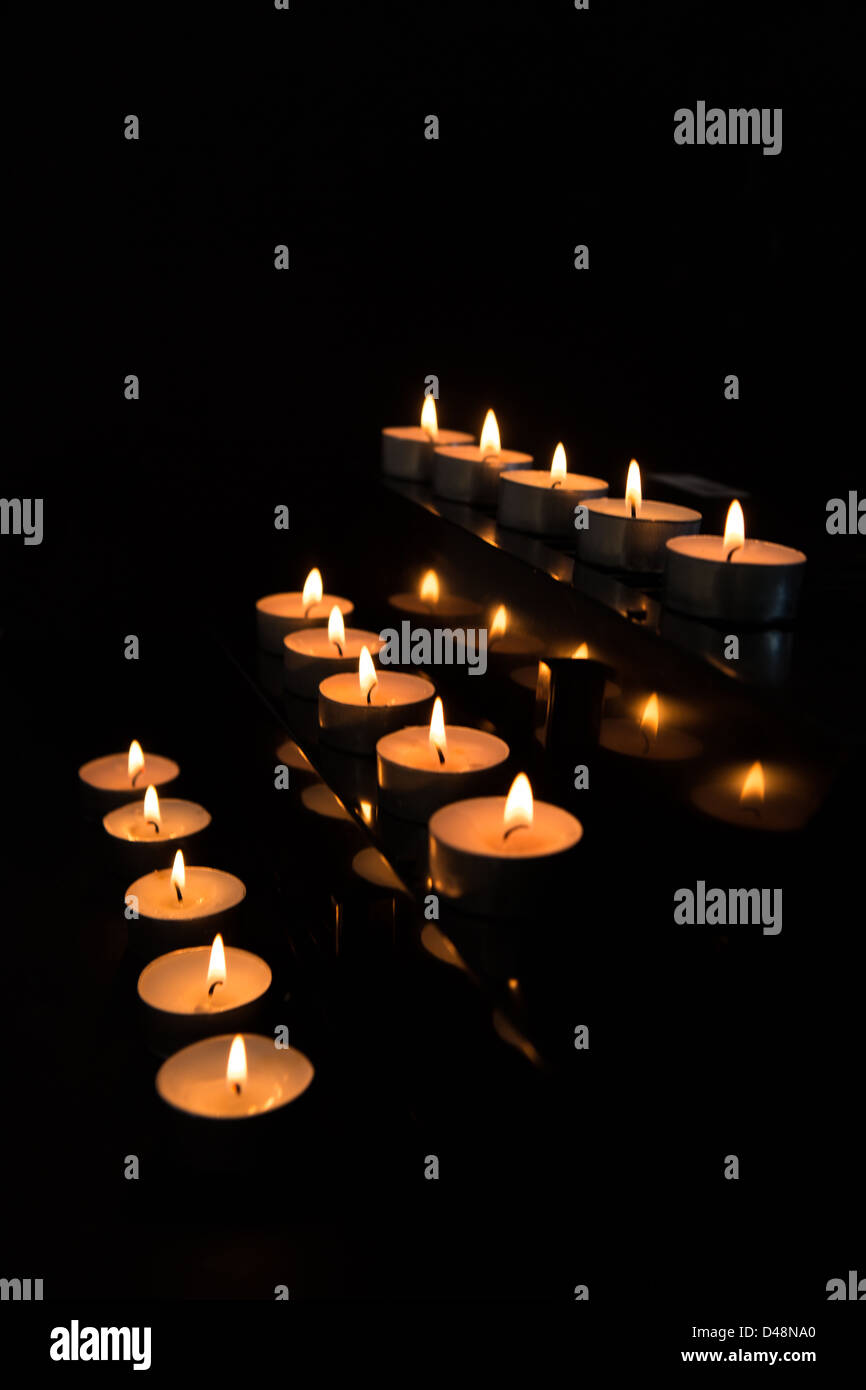 Candles at the alter lighting up the darkness - Stock Image