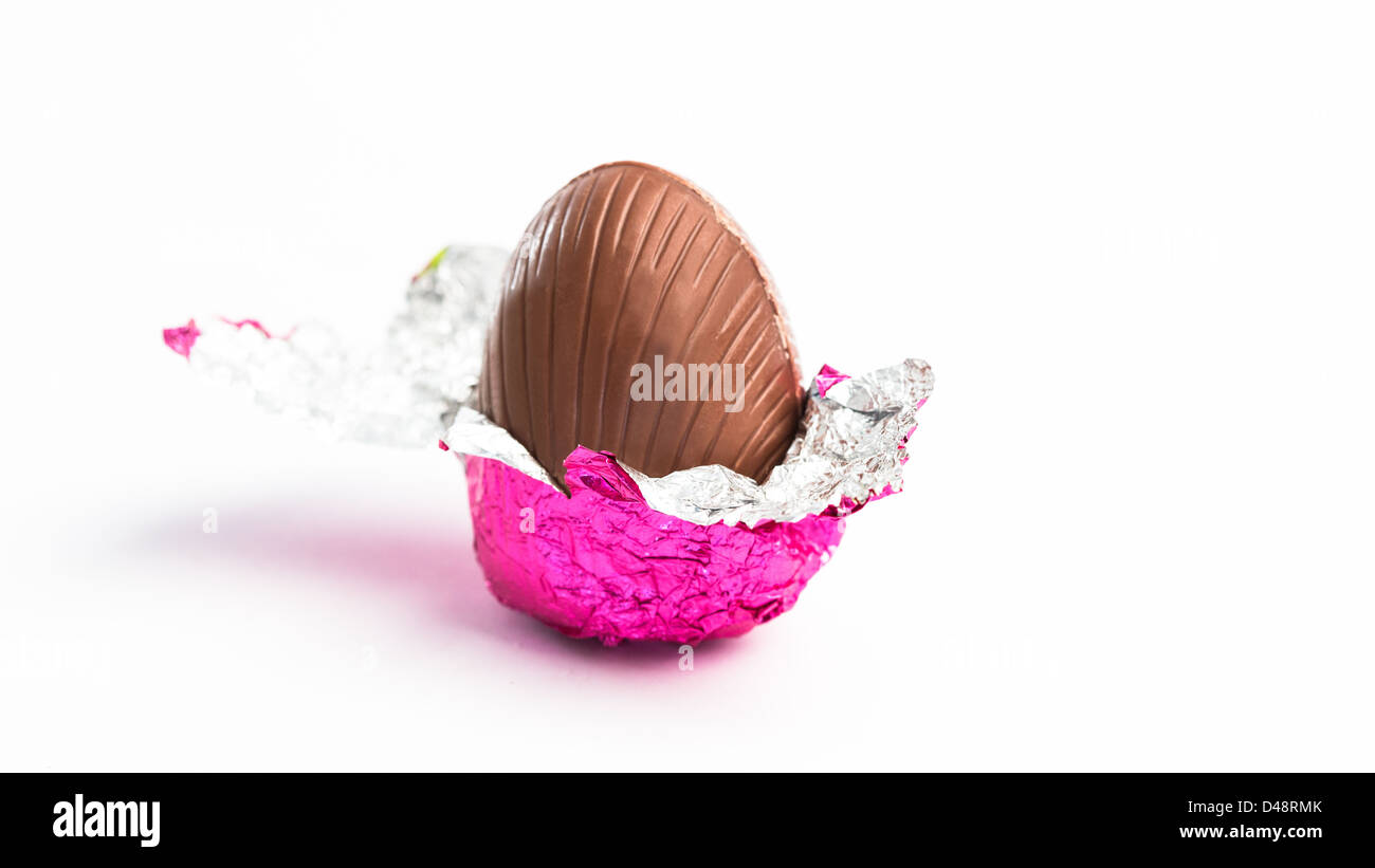 Easter egg unwrapped in pink foil - Stock Image