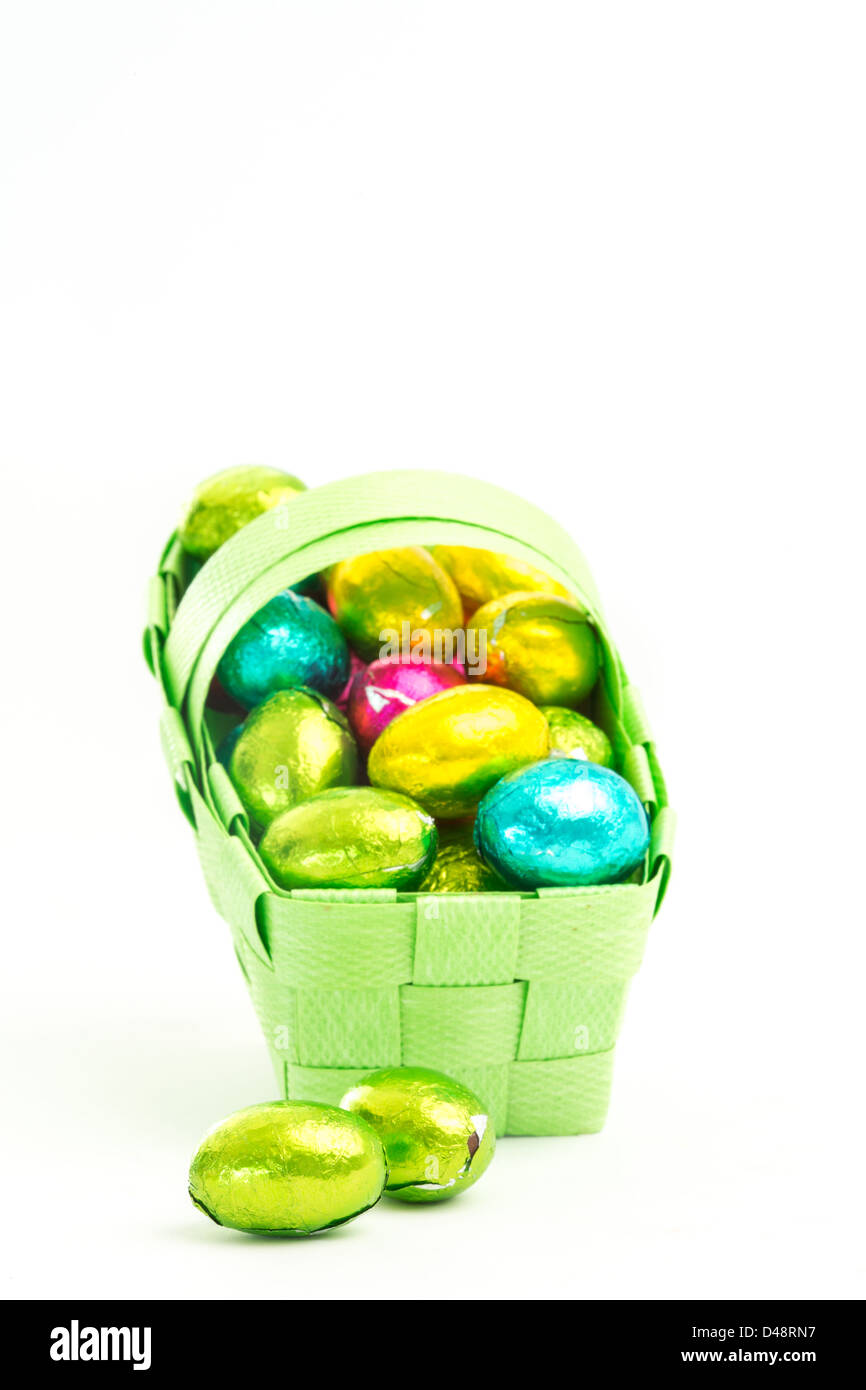 Foil wrapped easter eggs in a basket - Stock Image