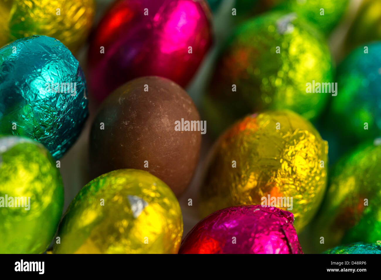 Colourful easter eggs with one unwrapped - Stock Image