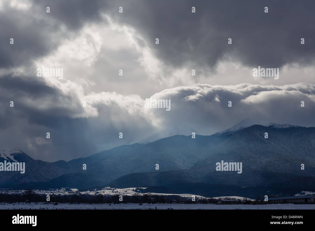 Gleam in clouds of a snow storm over mountains - Stock Image
