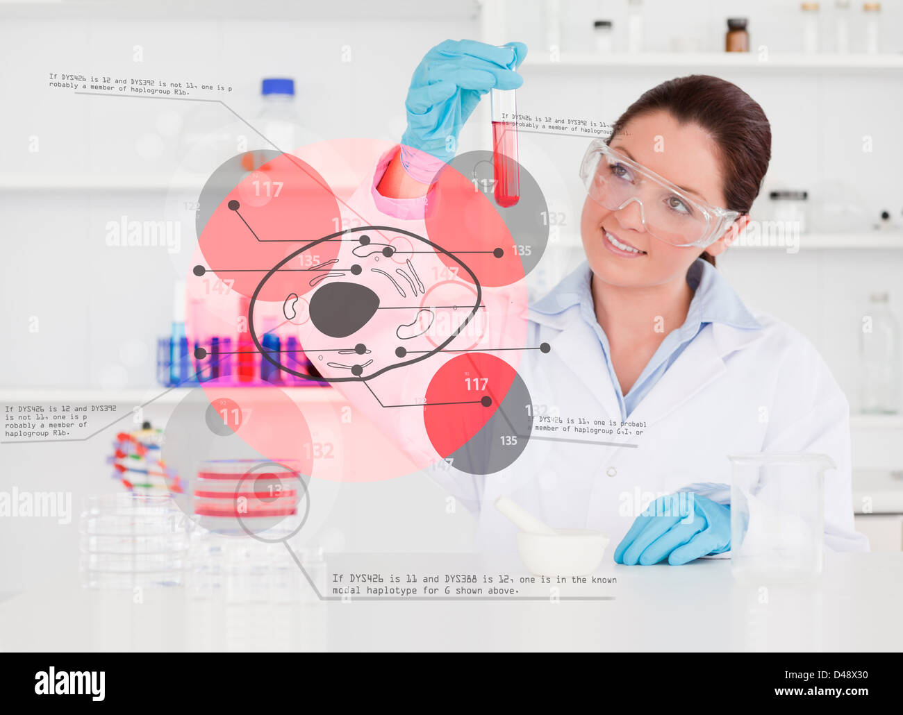 Smiling chemist looking at test tube of red chemical - Stock Image