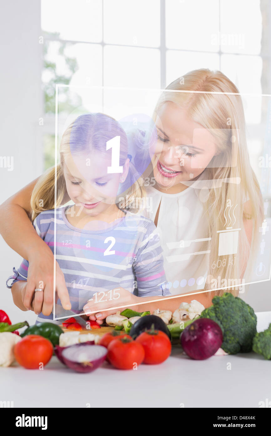 Mother and daughter chopping vegetables with holographic interface - Stock Image