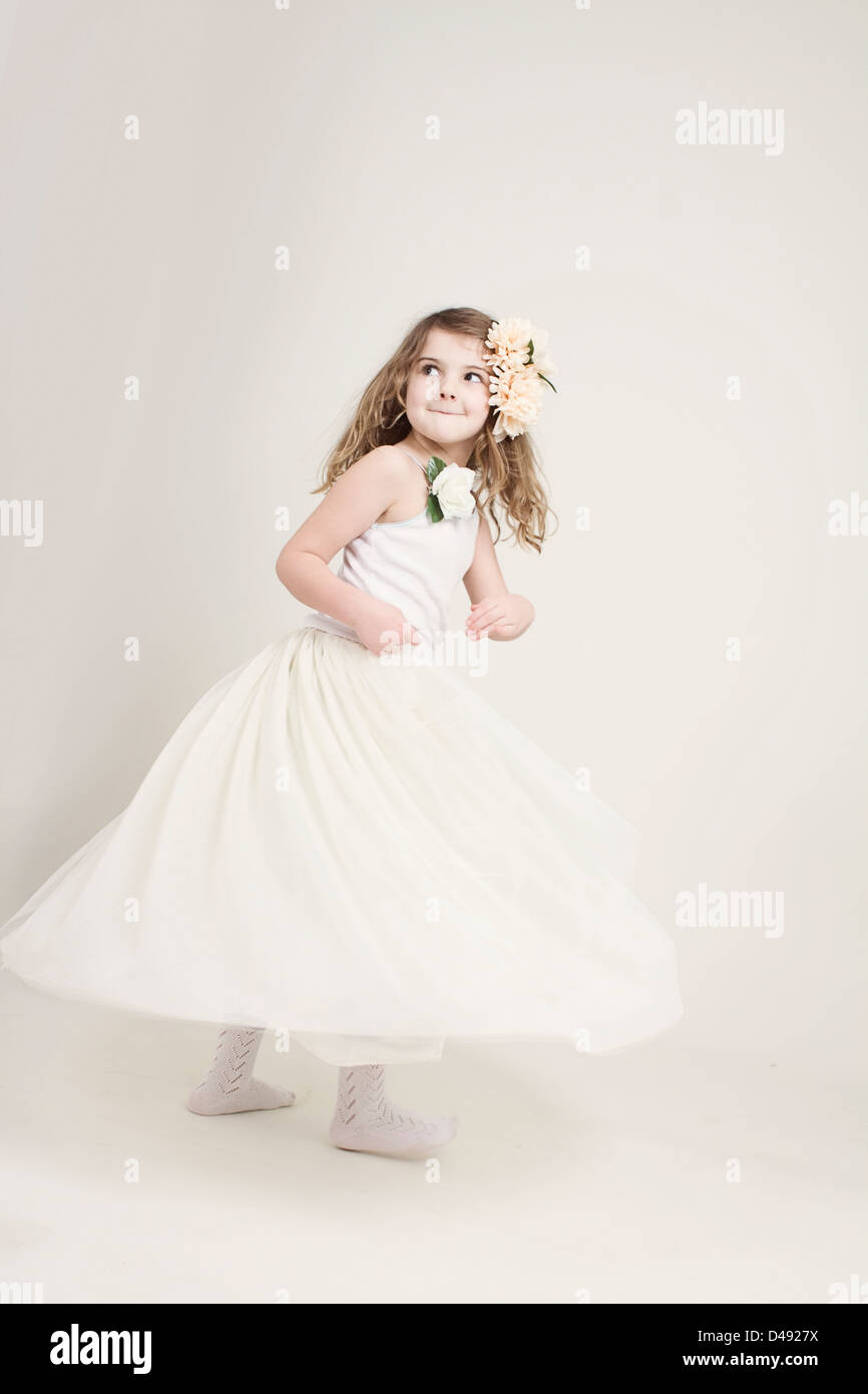 Angelic young Caucasian girl with pink flowers in her hair, twirling her skirts out and looking backwards past the - Stock Image