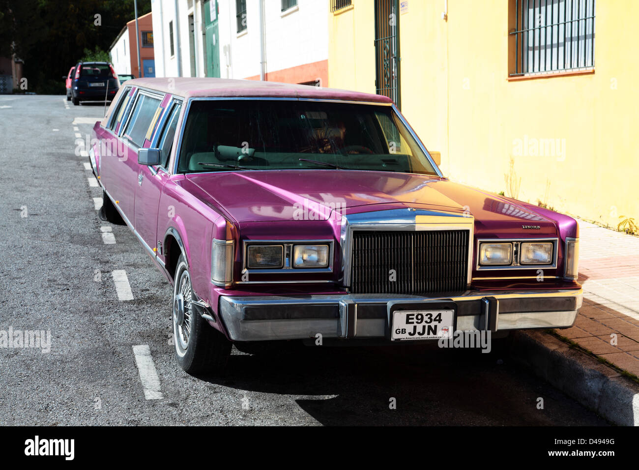 purple Lincoln continental stretched limousine parked on road side - Stock Image