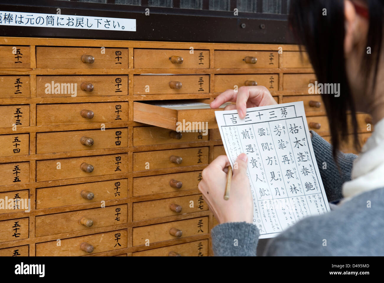 Omikuji paper oracle removed from numbered drawer at Sensoji Temple tells one what the future holds,a good or bad - Stock Image