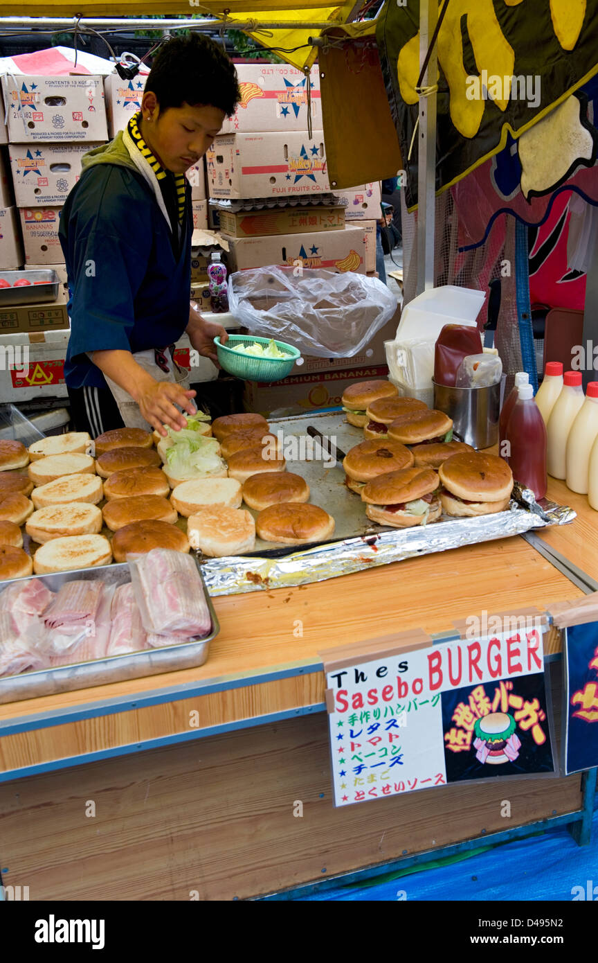 A food vendor at a festival in Japan is selling what he thinks western food should be...a giant-size hamburger fit - Stock Image