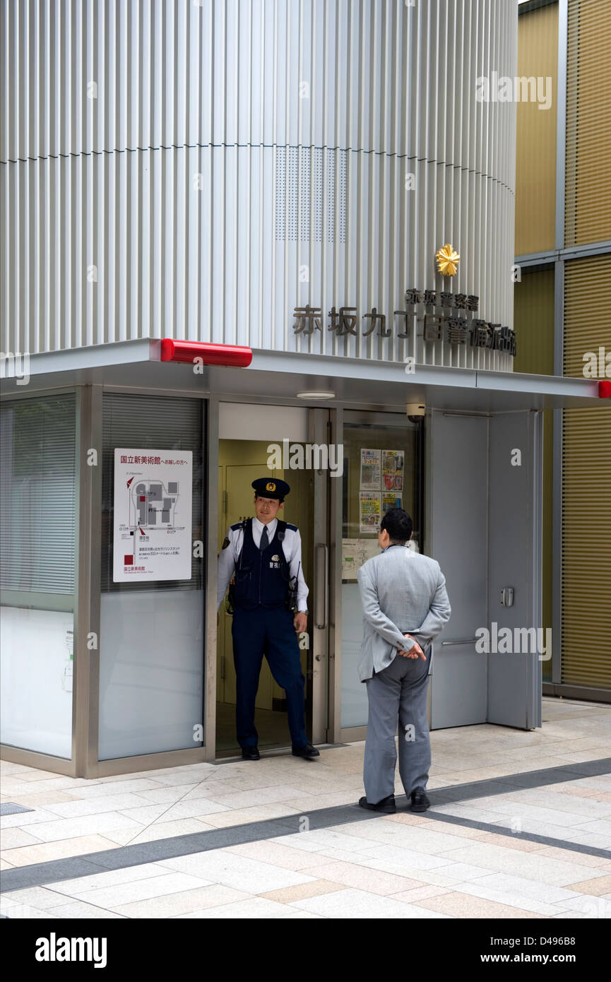 Pedestrian stops by a 'koban' police box to ask a question. Police koban are a common fixture in the Japanese - Stock Image