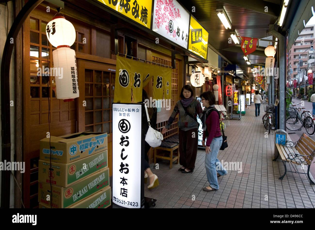 Patrons entering a manjayaki restaurant, where one can enjoy Japanese okonomiyaki style pizza in the Tsukishima, - Stock Image