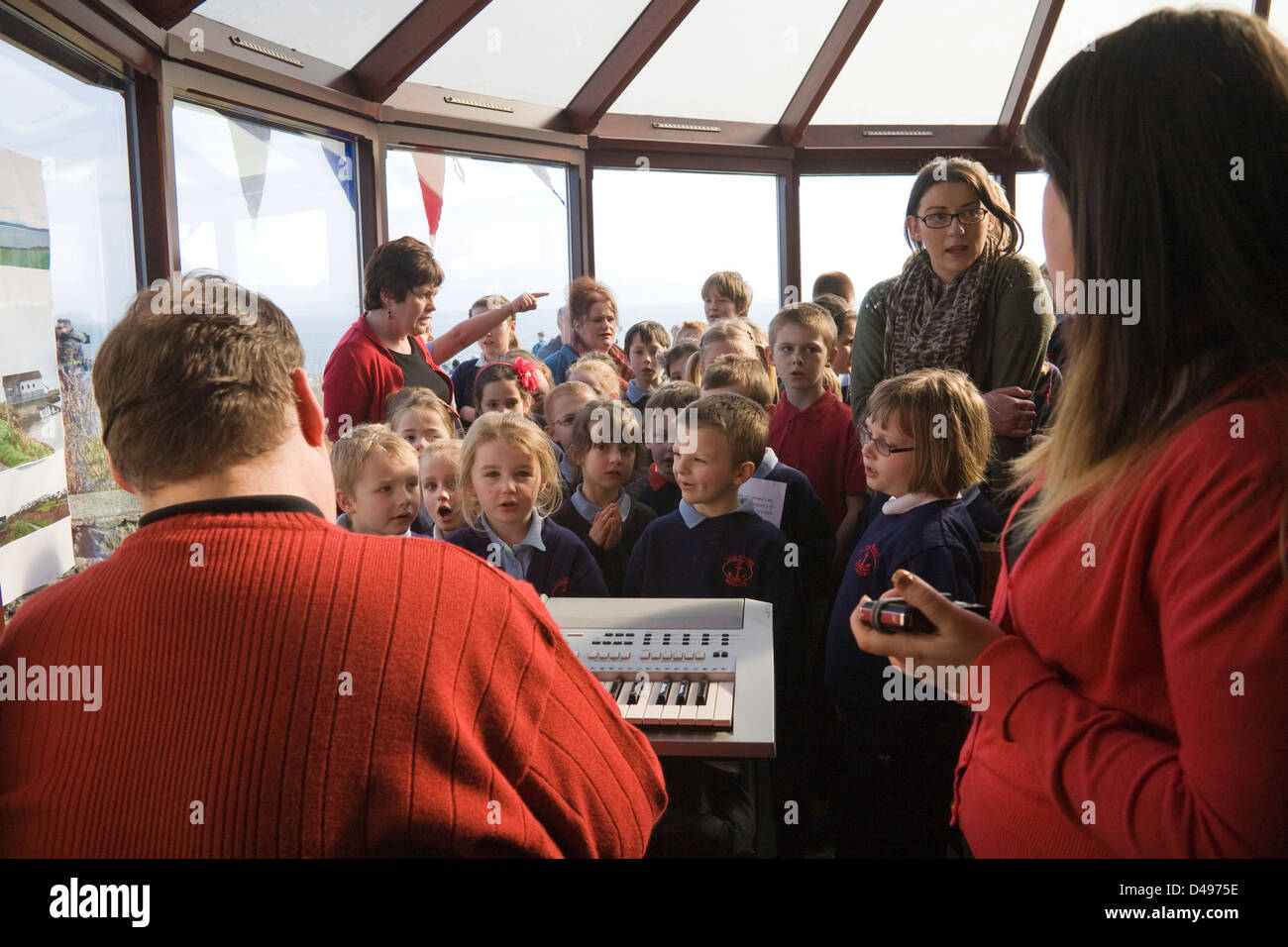 Moelfre Isle of Anglesey North Wales Local school children performing  Sea Watch Centre accompanied by teacher playing - Stock Image