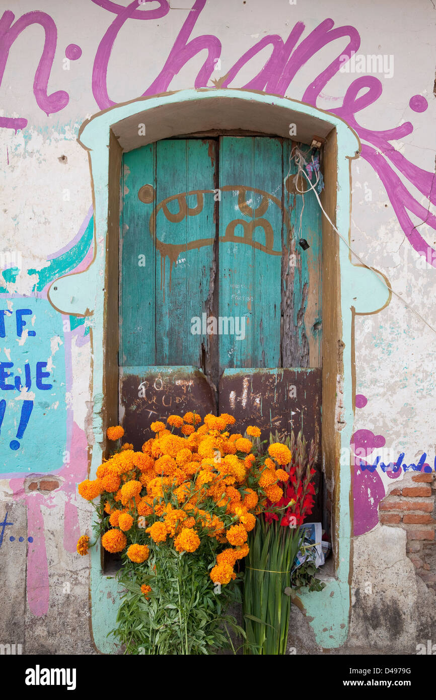 Bouquets of flowers in front of weathered doorway surrounded by colorful graffiti in Ocotlan, Oaxaca, Mexico. - Stock Image