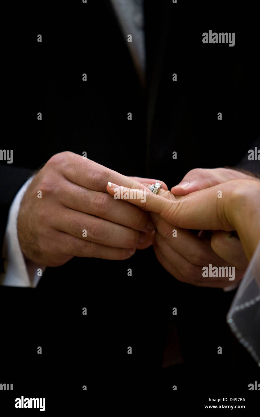 A groom places a ring onto his brides finger during a wedding ceremony. - Stock Image