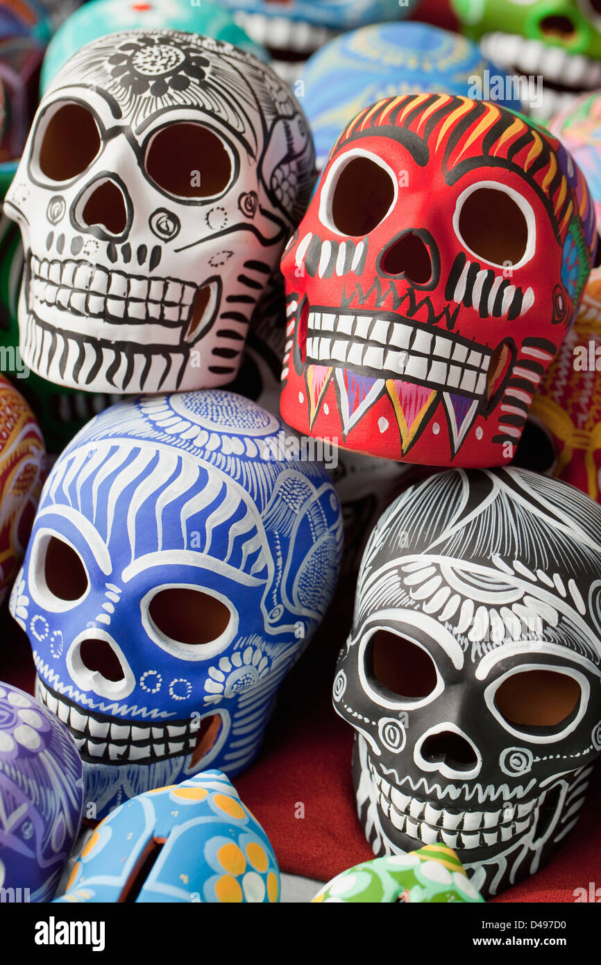 Rows of handpainted ceramic skulls for sale at Zocalo during Day of the Dead, Oaxaca, Mexico. - Stock Image
