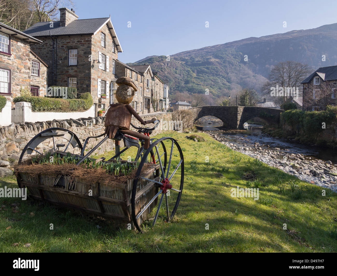 View along Afon Colwyn River to old bridge with unusual tricycle flower planter on riverside in Beddgelert, Snowdonia, - Stock Image