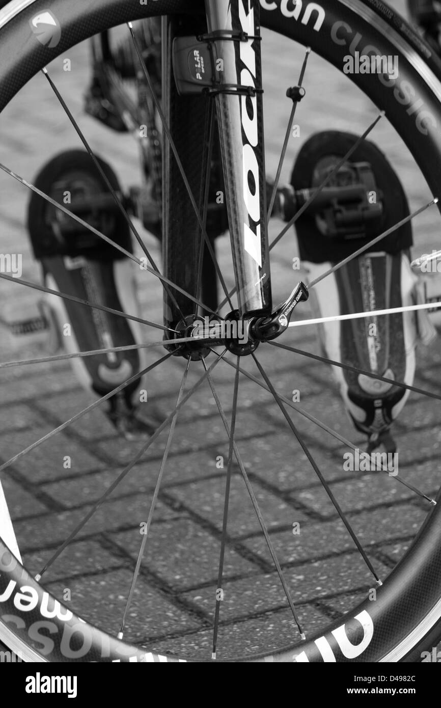 Cycling road shoes clipped in and seen through front wheel - Stock Image