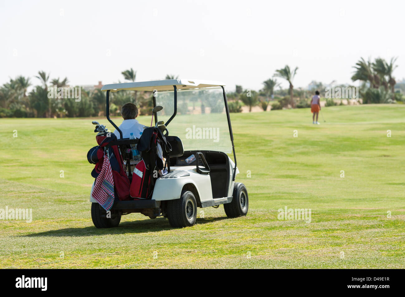 Electric golf buggy being driven on the fairway with golfer in the distance - Stock Image