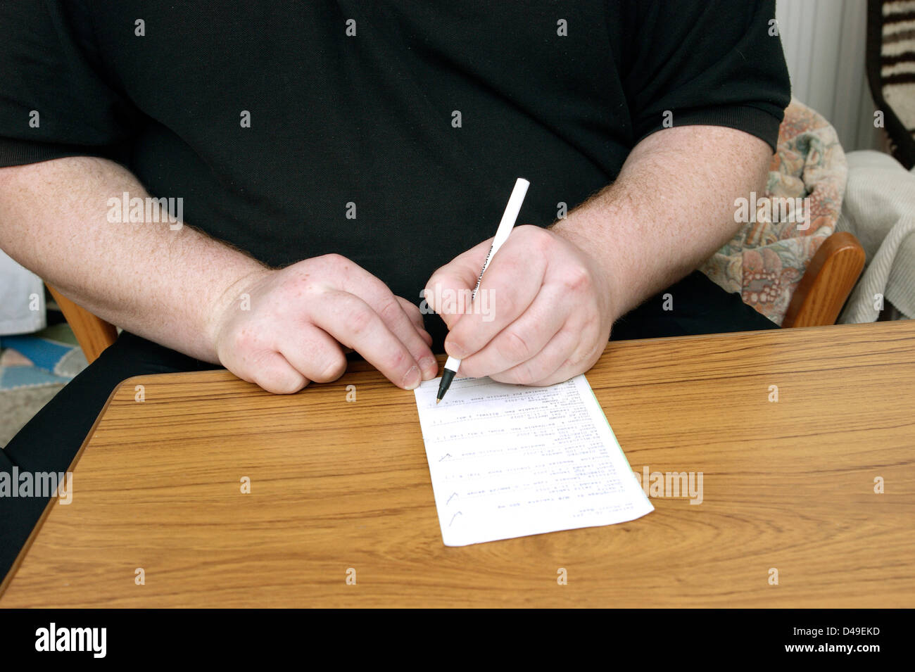 Man filling in form requesting repeat prescription / prescriptions - Stock Image