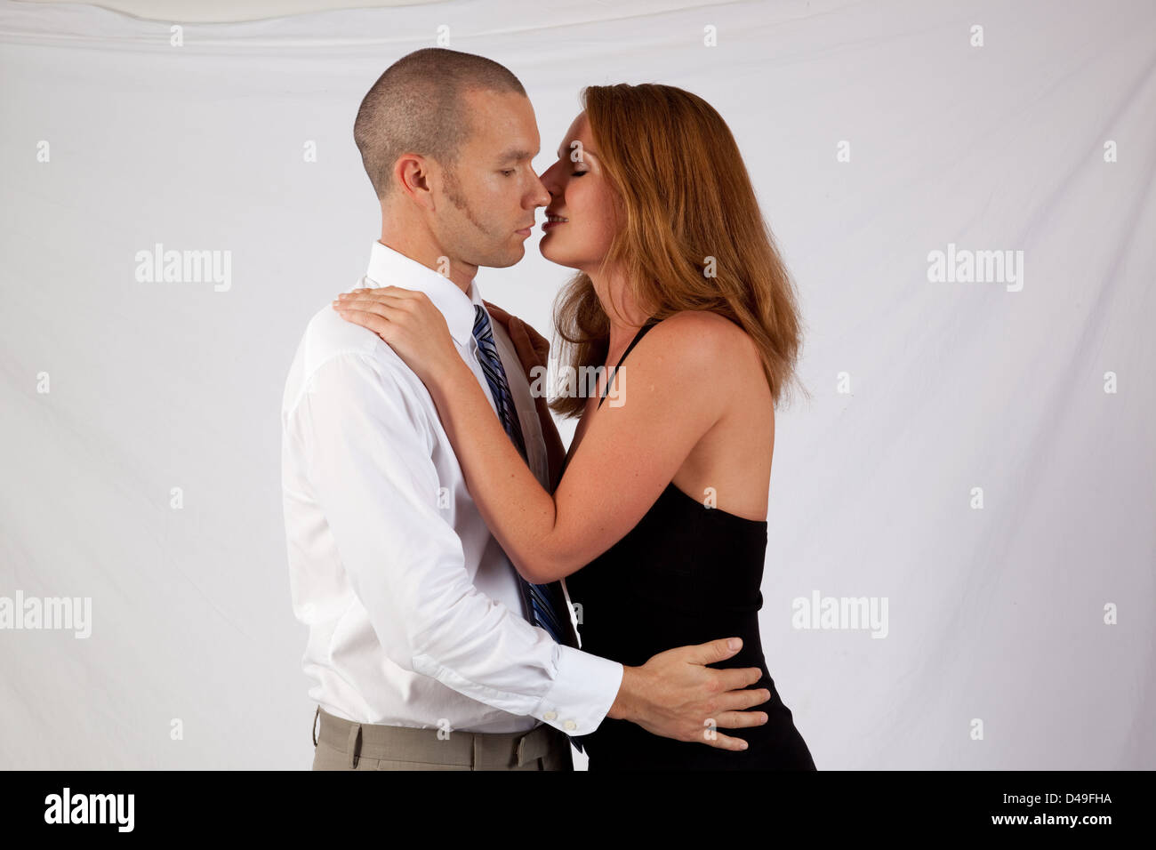Cute  couple standing in a romantic embrace, with her hand on his shoulder, and heads tilted together as if for - Stock Image