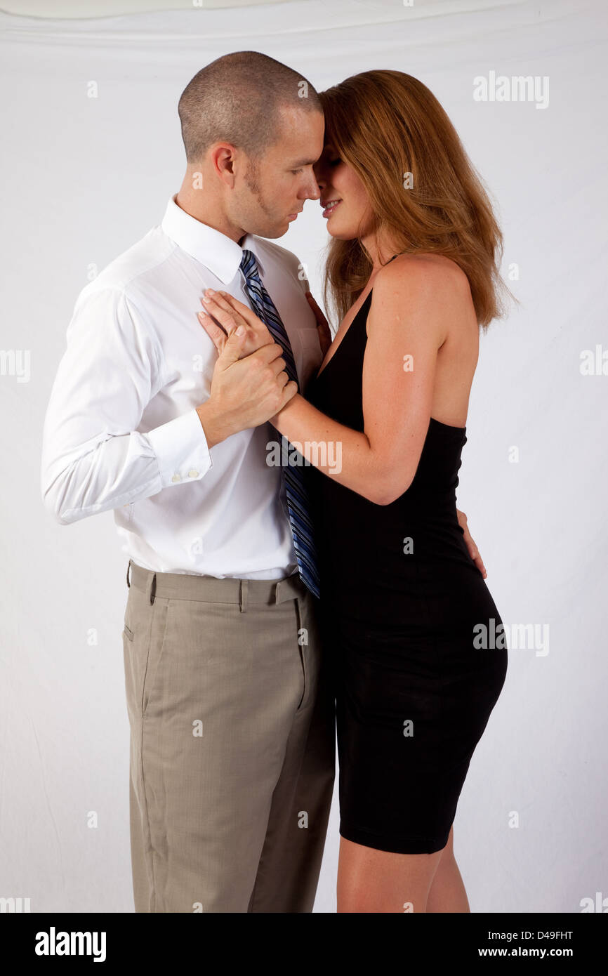 Cute  couple standing in a romantic embrace, with her hand on his chest, and heads tilted together as if for a kiss - Stock Image