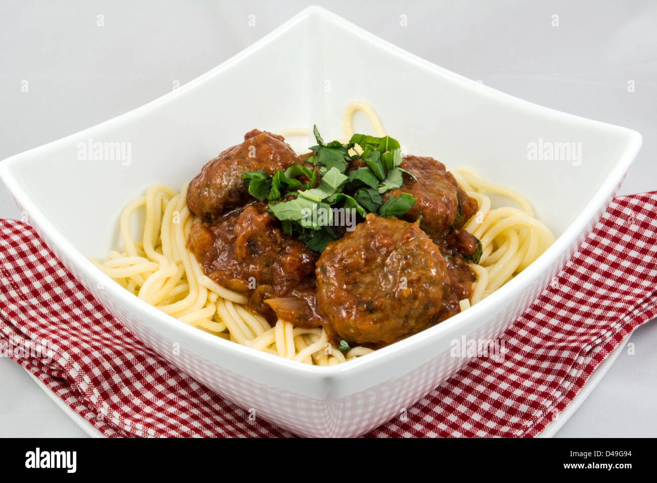 Meatballs with tomato sauce and spaghetti in a white pasta bowl, sitting on a red, gingham cloth - Stock Image