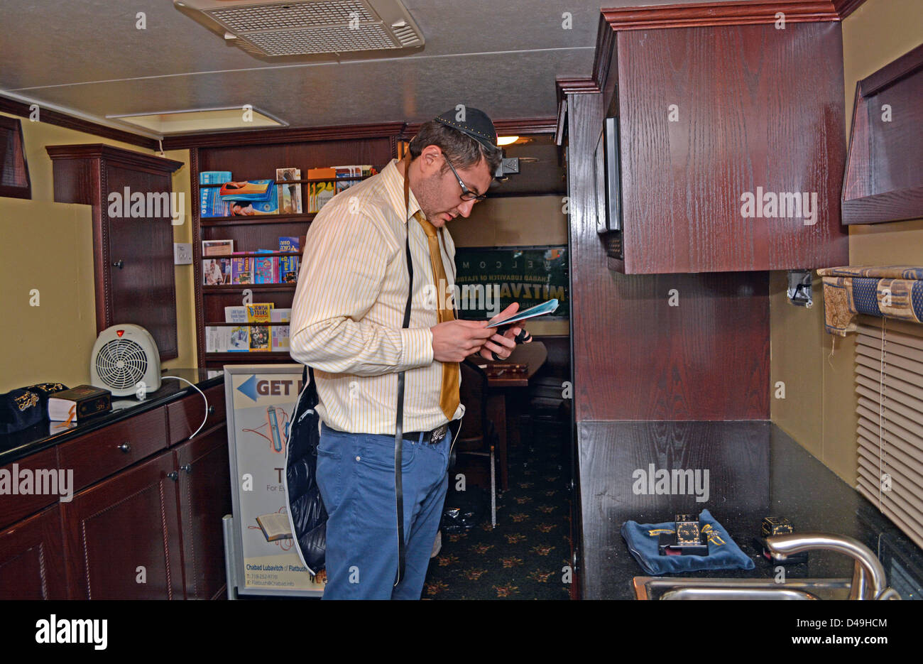 Inside a MItzvah tank in Brooklyn, a non-observant Jew puts on teffilin (phylacteries) and recites prayers. - Stock Image