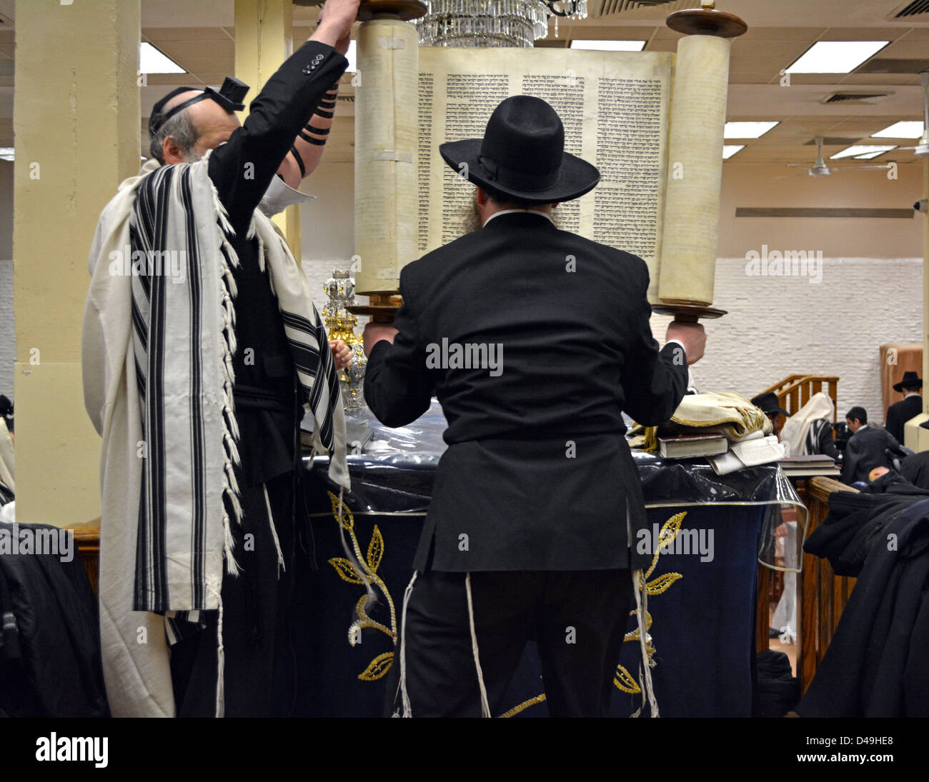 During morning services at Lubavitch Headquarters a worshiper lifts the Torah prior to it being returned to the Stock Photo