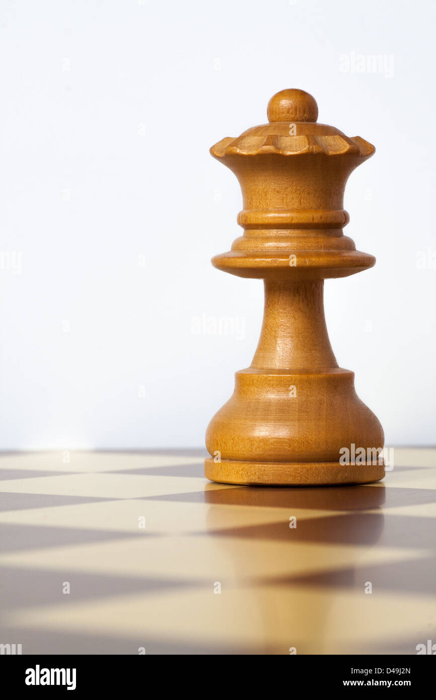 closeup of chess queen piece over chessboard - Stock Image