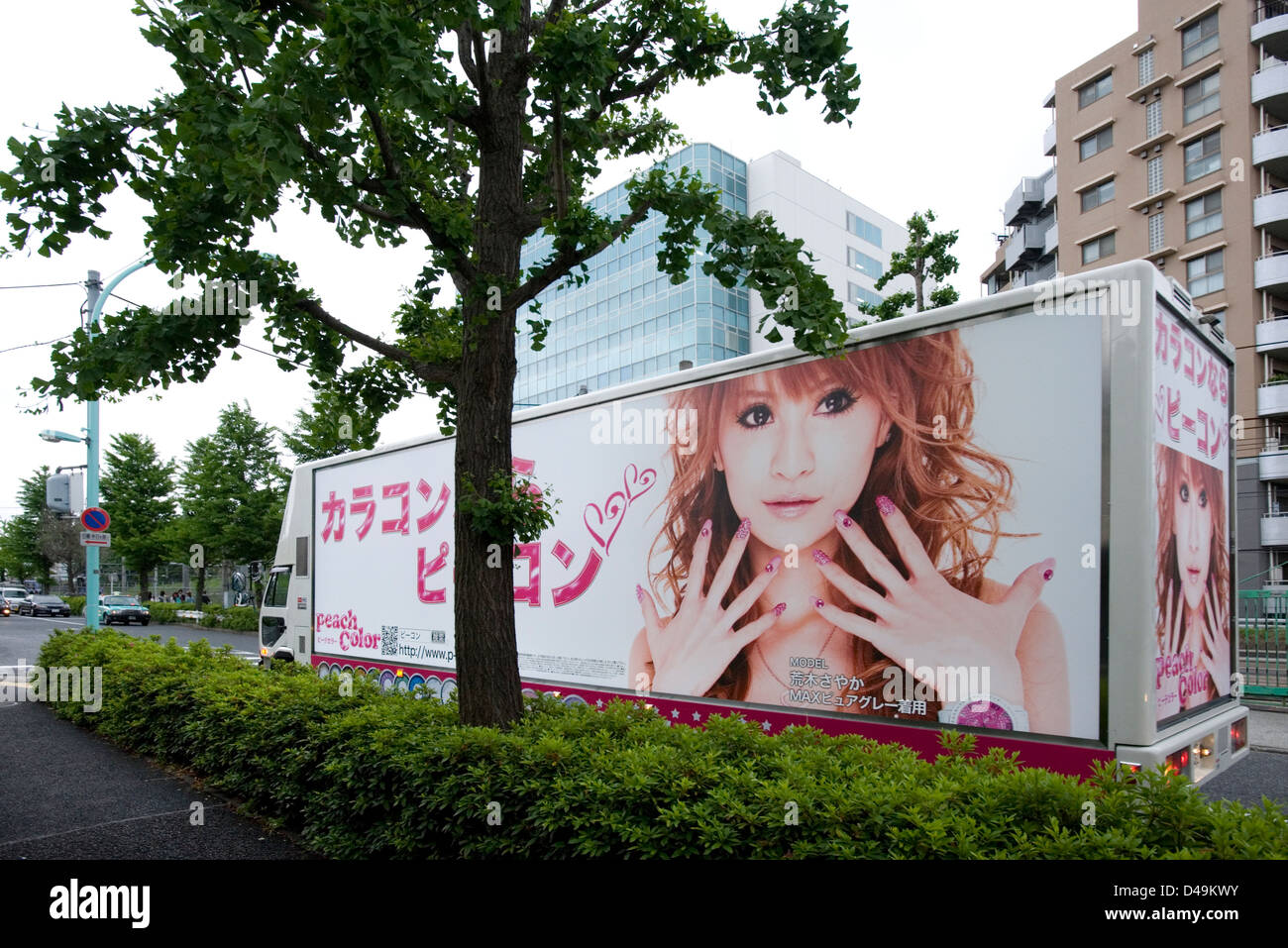 A large billboard sign truck advertising young girl's fashion passing by on the street of Shibuya, Tokyo. - Stock Image