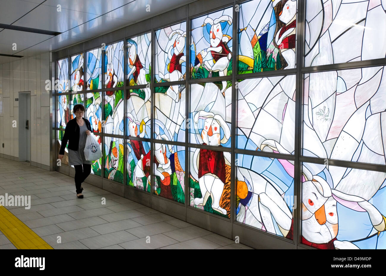 An illuminated stained glass art wall brightens an underground passageway in the Metro subway system of Tokyo. - Stock Image