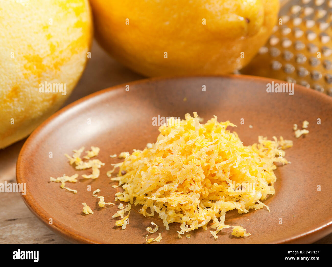 Lemon ingeredient zest on brown plate - Stock Image